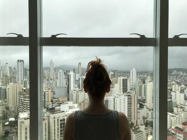 žena pozerajúca sa von z okna