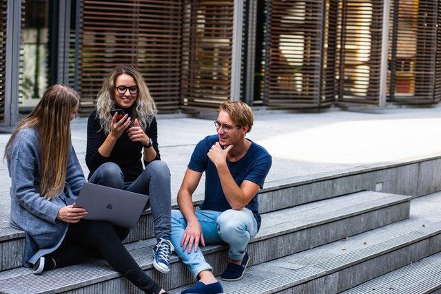 Traja ľudia sedia na chodoch a rozprávajú sa
